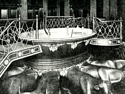 A black and white photo of a baptismal font supported by oxen.