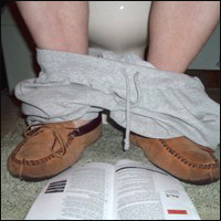 A man sitting on the toilet with his shorts round his ankles.