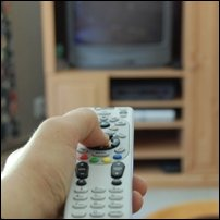 A hand pointing a remote control at a television set.