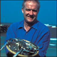 Master seafood chef Rick Stein holding out a platter of fresh crabs.