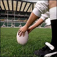 A rugby player places the ball on the ground, ready to take a kick.