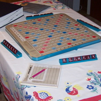 A Scrabble set up for four players on a table