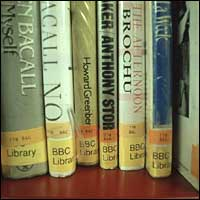The spines of a selection of books on a shelf.