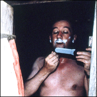 Reporter Allan Little shaving in Sierra Leone.
