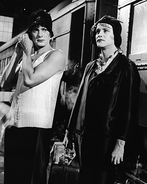 Actors Tony Curtis and Jack Lemmon standing on a train platform in a still from the film Some Like It Hot