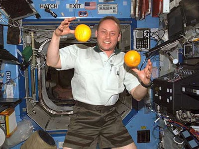 An astronaut juggling fruit on the International Space Station