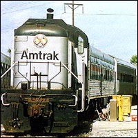 A large American locomotive pulls out from a station.