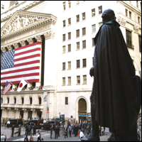 A statue of George Washington looks on as a giant US flag hangs on the exterior of the New York Stock Exchange, Wall Street.
