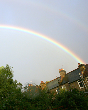A rainbow arcing across the sky above some houses