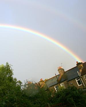 A rainbow arcing across the sky above some houses