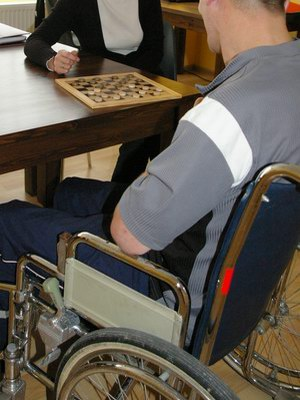 A person in a wheelchair playing draughts/checkers.