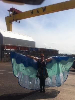 A large blue winged costume under the shadow of a Belfast shipyard crane
