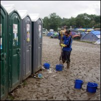 A cleaner with mop and bucket stands outside Glastonbury Festival toilets.