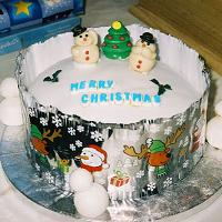 A Christmas cake decorated with edible snowmen and the words 'Merry Christmas' written on it in icing.